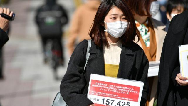 戴着口罩的能條桃子手持请愿书,上面写着157.425,那时收集到的签名数。