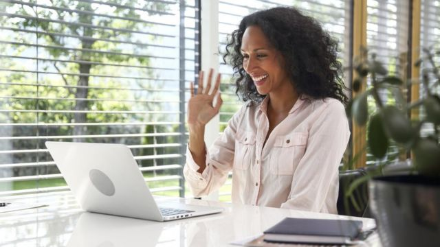Woman waves to her laptop during a videoconference at home