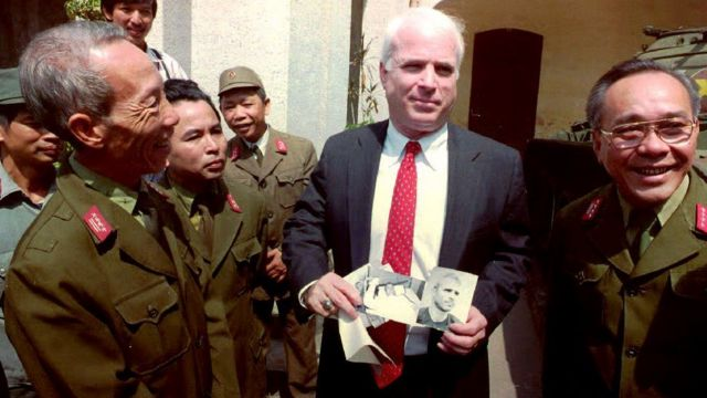 .S. Senator John McCain (C), R-Ariz., a member of the Senate Select Committee on servicemen listed as missing in action (MIA's) in Southeast Asia, holds up photos of himself, as a 30-year-old man wounded and captured in 1967 in North Vietnam, outside the Army Museum in Hanoi 19 October, 1992.