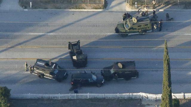 窓が撃ち抜かれた黒いSUVを警察が取り囲み、銃撃戦となった(2日)