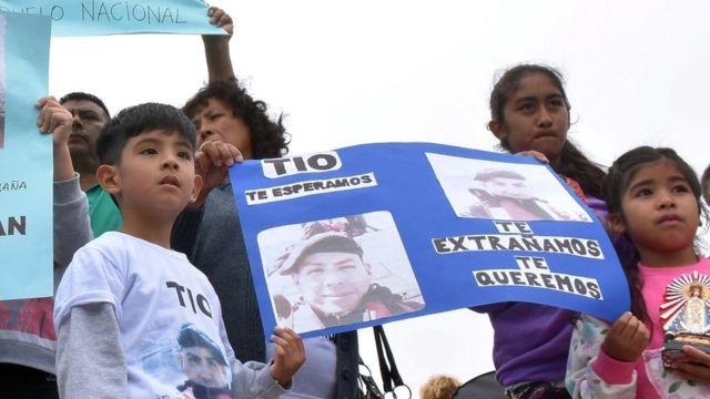 Duas crianças seguram um cartaz com fotos do tripulantes do Ara San Juan e os dizeres: 'tio, te esperamos, sentimos sua falta'