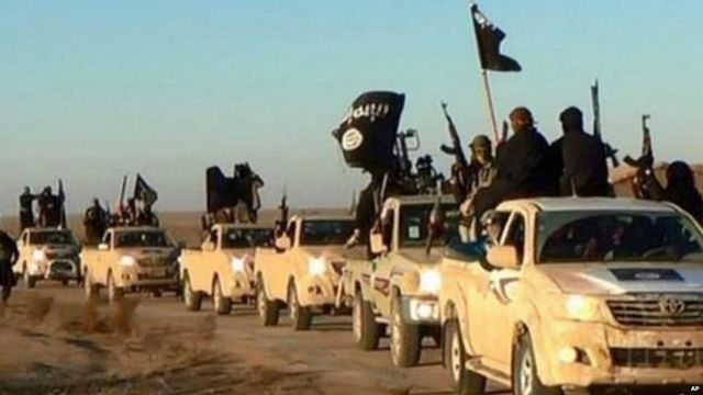 Undated photo shows militants of the Islamic State group hold up their weapons and wave its flags on their vehicles in a convoy on a road leading to Iraq, while riding in Raqqa city in Syria