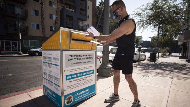 Un hombre deposita un voto en un buzón en la calle