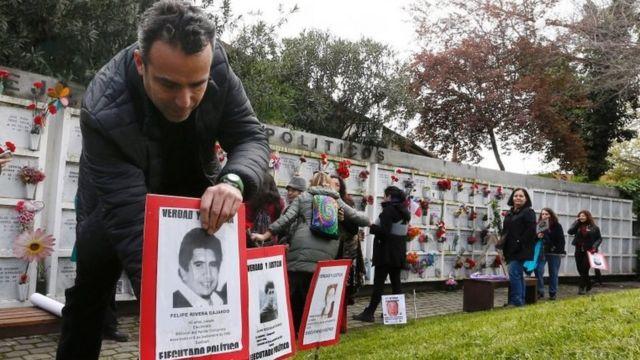 """Un hombre con un póster de una persona que desapareció durante el gobierno de Augusto Pinochet, durante una manifestación por el aniversario del golpe de 1973. El cartel dice """"ejecutado político""""."""