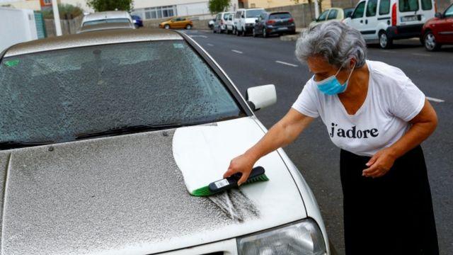 Una mujer limpia las cenizas de su auto en La Palma.