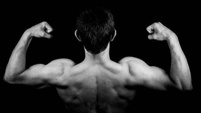 Homem tensiona músculos das costas