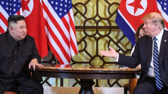 """US President Donald Trump (R) speaks during a meeting with North Korea""""s leader Kim Jong Un"""