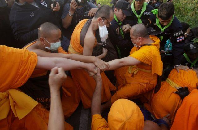 Budist keşişler Tayland polisiyle çatışan bir keşişe yardım ediyor.
