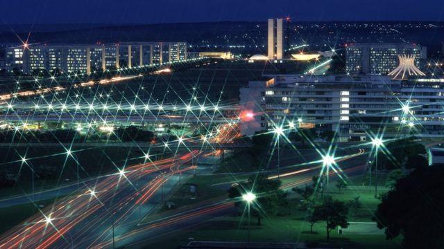 A Esplanada dos Ministérios à noite, iluminada por luzes de carros e postes