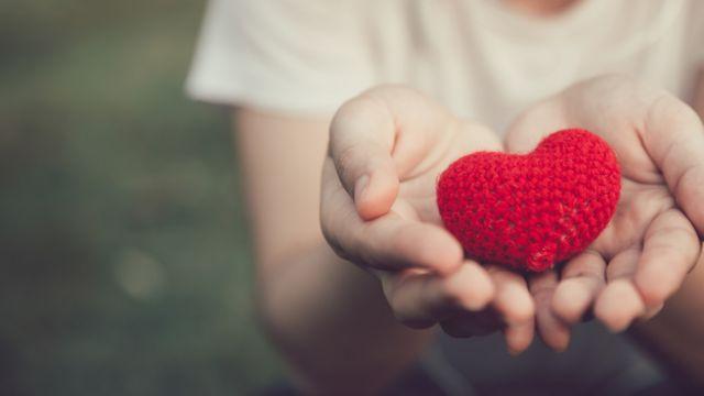Manos abiertas con un corazón de lana