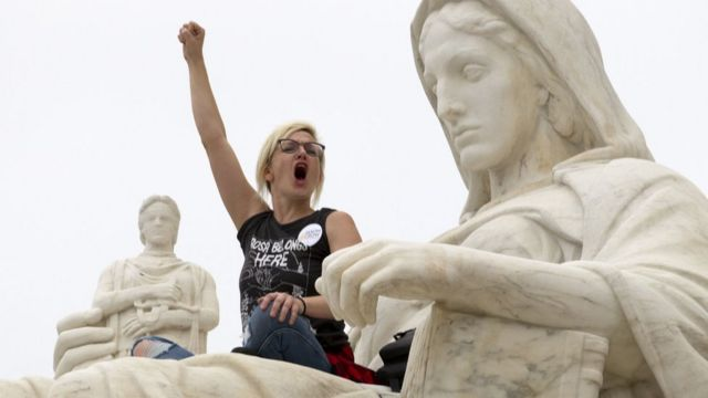 """Demonstrator Jessica Campbell-Swanson of Denver, Colorado, sits on the lap of the """"Contemplation of Justice"""" statue outside the US Supreme Court in Washington DC, October 6, 2018"""