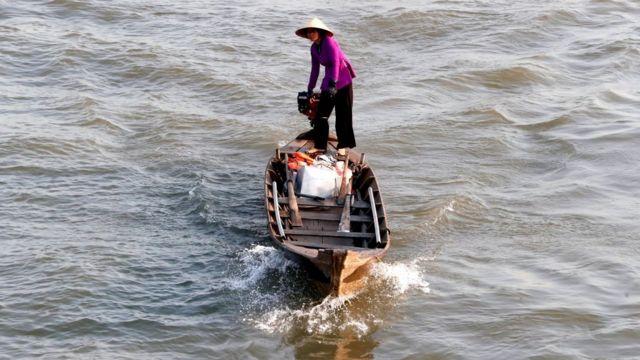 Người phụ nữ đi thuyền đến chợ nổi Cái Bè, Việt Nam