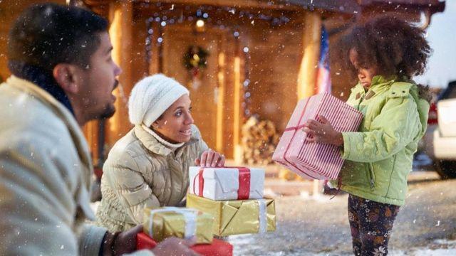 أب وأم يقدمان هدية لطفلة صغيرة