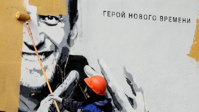Коммунальный работник закрашивает граффити с Навальным в Санкт-Петербурге