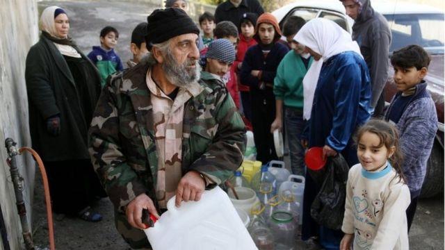 Habitantes de Damasco llenan tanques con agua.