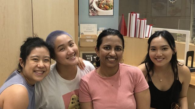 Stephanie sits together with three other Asian women who form her leadership team.