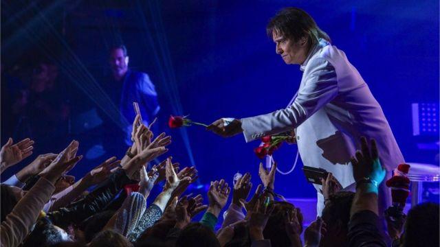 Roberto Carlos entrega flor para fas