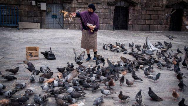 Una señora alimenta a las palomas en la Plaza de San Francisco de Quito, Ecuador.