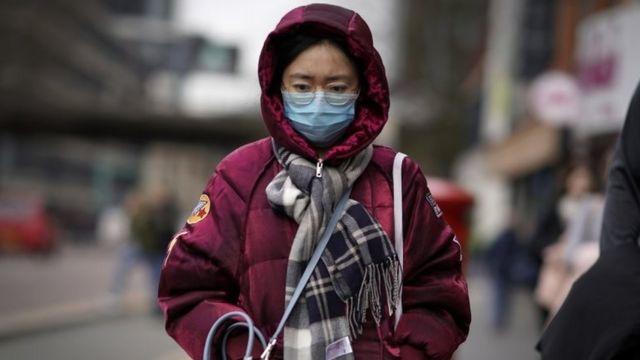 Mulher caminha em Londres com máscara
