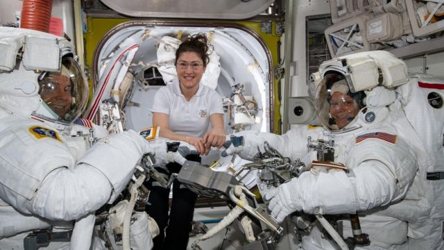 Christina Koch (centre) assists fellow astronauts Nick Hague (left) and Anne McClain in their spacesuits