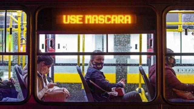 """Pessoas de máscara em ônibus onde um letreiro luminoso diz """"use máscara"""""""