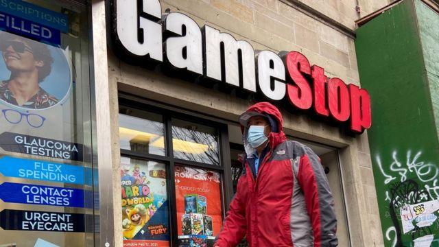 A person walks past a GameStop store