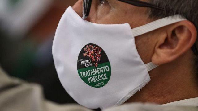 Homem de perfil com máscara dizendo: 'Sou médico apoio tratamento precoce'