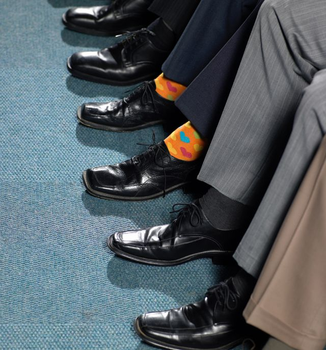 Un hombre con medias naranjas, entre pies con medias oscuras