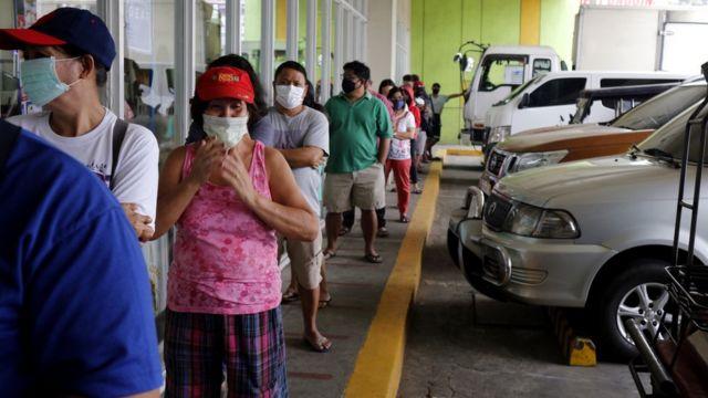 Clientes em fila com distanciamento do lado de fora de uma loja nas Filipinas.