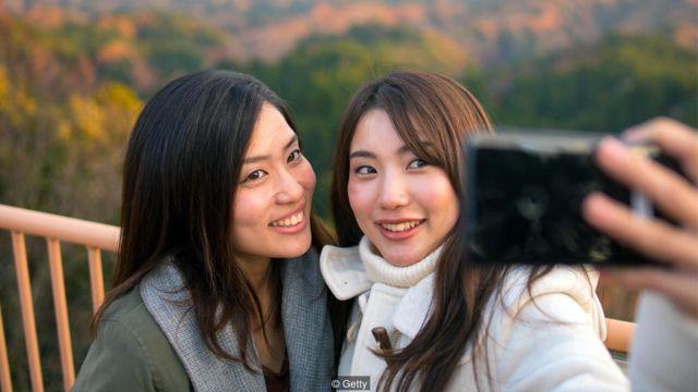 Imagem mostra duas mulheres fazendo selfies