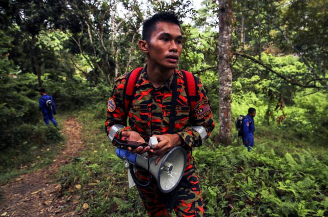 An officer from the Malaysian Fire and Rescue Department takes part in the search for 15-year-old Nora Quoirin