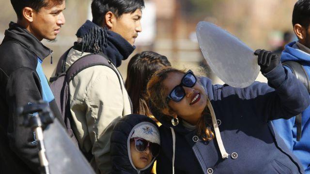 काठमाण्डूबाट सूर्यग्रहण हेर्दै महिला र बालक
