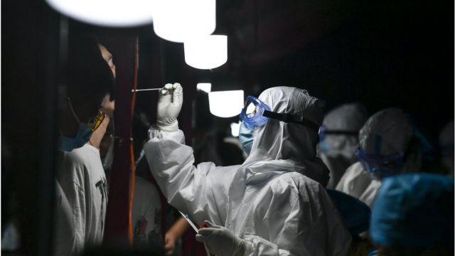 Em sala escura, profissional paramentado aplica cotonete no nariz de pessoa