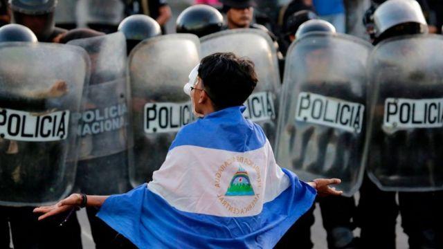 Manifestante cubierto con la bandera de Nicaragua