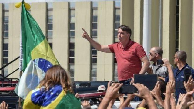 Bolsonaro em meio a manifestantes e ao lado de bandeira do Brasil, com dedo em riste