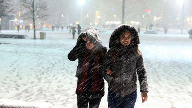 Karda yürüyen iki kişi