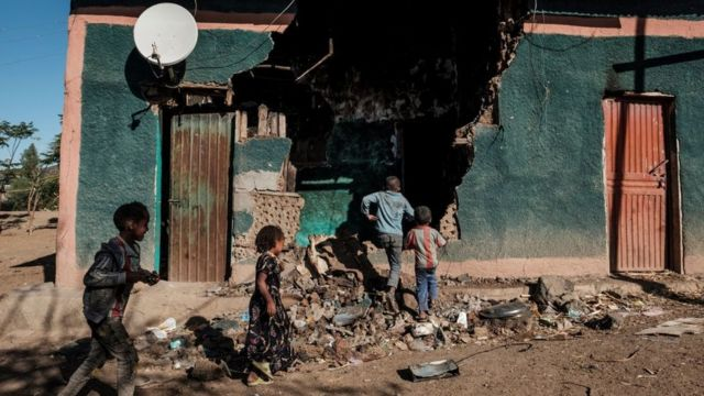 Children play in front of a house that was damaged during clashes that broke out in Ethiopia's Tigray region, in the village of Bisober, on December 9, 2020.