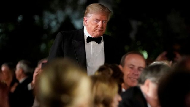 Trump em pé, em meio a outras pessoas sentadas, durante evento de gala
