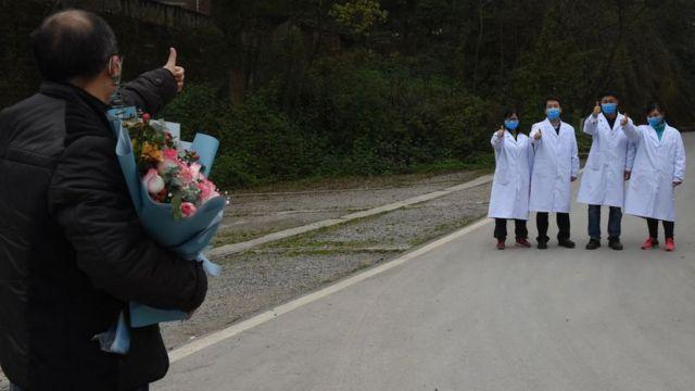 Un paciente curado de covid-19 saluda a los trabajadores médicos cuando es dado de alta del Centro de Salud Pública de Chongqing el 15 de marzo de 2020 en Chongqing, China.