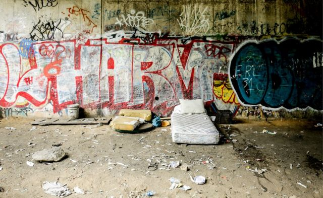 A bed sits empty on the side of the tracks, surrounded by used needles