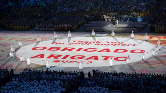 """A huge message is unveiled in the main arena reading """"Obrigado Arigato"""" the Portuguese and Japanese words for thank you."""