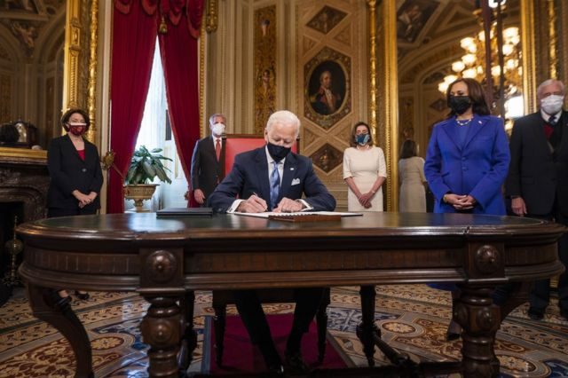 President Biden signs documents with Vice President Kamala Harris by his side