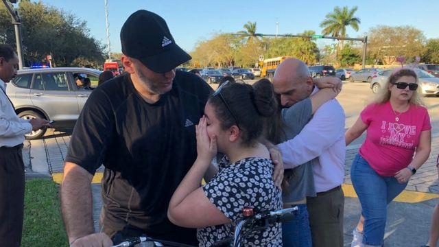 Varias personas se abrazan afuera de la secundaria Stoneman Douglas