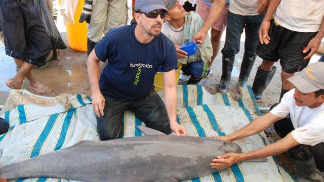 Fernando Trujillo con un delfín y pobladores locales