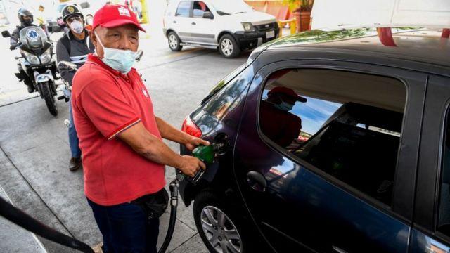 Un empleado de una estación de gasolina llena el tanque de un auto.