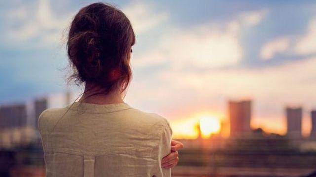 Una mujer de espaldas a la puesta de sol.