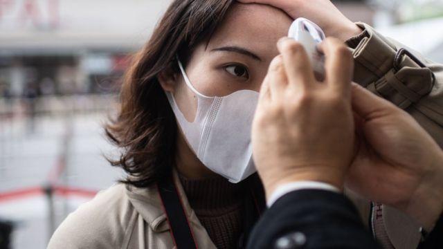 mulher no japao tem sua temperatura corporea medida
