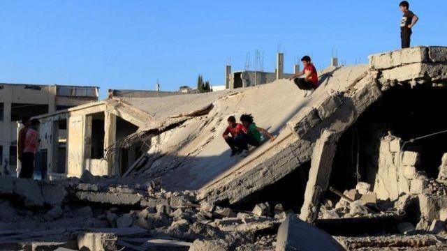 Niños se deslizan sobre un techo derrumbado en la ciudad de Daraa.