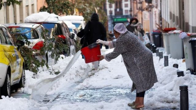 A woman throws water on a snow-covered street, following heavy snowfall, in Madrid, Spain January 11, 2021