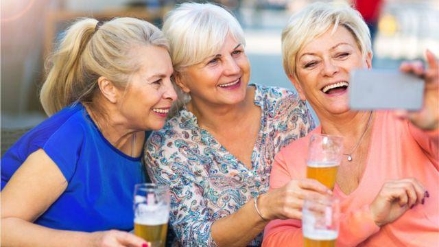 mulheres tirando uma selfie e com copos de cerveja na mão